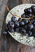 Purple grapes with drops of water on a plate