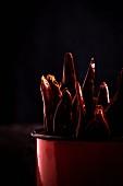 Würzige rote Chilischoten in Schale auf altem Holztisch