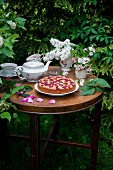 Simple strawberry cake with tea served outside on a garden table