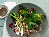 Lamb fillet with figs, spring onions, pine nuts and a salad