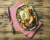 Oven roasted whole chicken with onion, apples and sage in serving tray over rustic wooden background