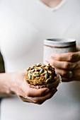 A woman is holding a freshly baked Maple Sweetened Pumpkin Oat Muffin in her hand