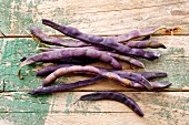 Purple beans on a wood background