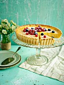 Lemon tart topped with berries with a slice taken out