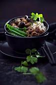 Veganer roter Quinoa und Reis mit Waldpilzen, Sojachunks, Kaiserschoten und schwarzem Sesam