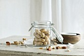 Peanuts in and next to a glass jar on a rustic kitchen table