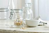 Pinienkerne im Glas und Mörser auf rustikalem Küchentisch