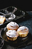 Modern pastries cruffins, whole and slice, with sugar powder served on black plate with sieve