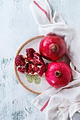 Ripe slice and whole pomegranates on ornate ceramic plate on kitchen linen towel over white wooden background