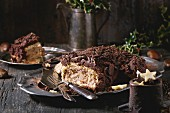 Sliced homemade Christmas chocolate yule log with chestnuts cream on vintage plate with forks