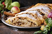 Close up of sliced homemade apple strudel with sugar powder on vintage metal tray