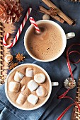 Two big cups of hot chocolate with a candy cane and marshmallows for Christmas