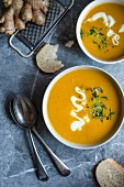 Two bowls of carrot, orange and ginger soup, view from above