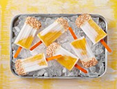 Mango and coconut ice lollies topped with white chocolate and desiccated coconut on a bed of ice cubes