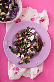 A salad with beetroot leaves, purple cauliflower and feta