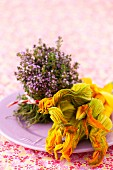 An arrangement of blossoming thyme and yellow courgette with flowers on a plate