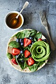 Mixed salad with spinach, berries and avocado rose with honey mustard dressing