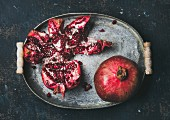 Fresh ripe pomegranate broken in pieces in vintage metal tray
