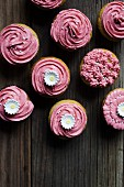 Pink iced cupcakes on a vintage board with flowers