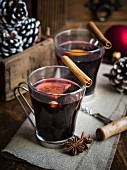 Two glasses of hot mulled wine on a rustic Christmas background