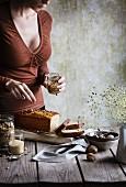 Woman putting muesli on the cake