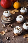 Pumpkin cupcakes with cream cheese frosting and walnuts.