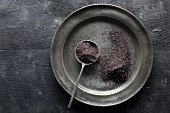 Poppy seeds on a tin plate and a spoon with a black background