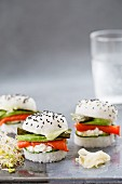 Three sushi burgers with smoked salmon, cucumber, fresh cheese, wasabi, nori and avocado