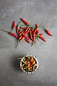 A bowl of chillis and scattered chillis (seen from above)