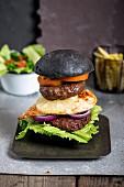 Rindfleisch, Huhn und Schweinefleisch-Burger in schwarzem Brötchen