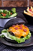 Beef burger with melted cheese in a black bun