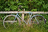 An old bicycle next to a fence in southern Sweden