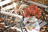Blumenvasen mit Hagebutten und mit Schilf geschmückt