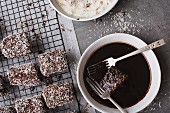 Making Lamingtons - dipping in chocolate icing