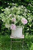 Kerbelblüten und Pfingstrosen im Emaileimer auf einem Gartenstuhl