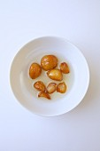 Roasted Garlic in olive oil on a white plate