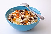 Yogurt with dried fruits, dates, almonds, walnuts, and papaya in a blue bowl on a white background