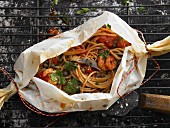 Spaghetti in parchment with shrimp and tomato sauce