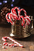Christmas candy cane in a traditional style gold mug with one whole can on the table with broken candy can pieces