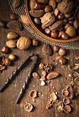 Verschiedene Nüsse in Holzschale mit altem Metall-Nussknacker auf rustikaler Holzplatte