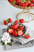 Fresh whole and halved strawberries in a bowl, decorated with a paper flower