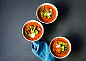 Chilled heirloom tomato gazpacho soup topped with avocado, cherry tomatoes, cilantro and a dallop of sour cream