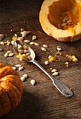 A hollowed out munchkin pumpkin, pumpkin seeds and a vintage spoon on a rustic wooden background