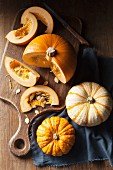 A piece of pumpkin on a wooden chopping board and munchkin pumpkins on a blue linen napkin