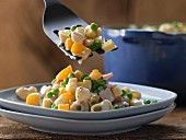 Pasta salad with ham, peas and orange