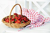 Fresh strawberries in a basket on a wooden table
