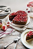 Chocolate cake in a shape of a heart with chocolate glaze and pomegranate seeds