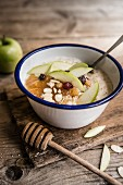 A bowl of porridge with apple puree, sultanas, almond, honey and apple slices