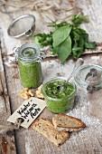 Herb and walnut pesto in glass jars