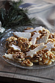 Butter cookies with walnuts and almond nibs on a glass plate